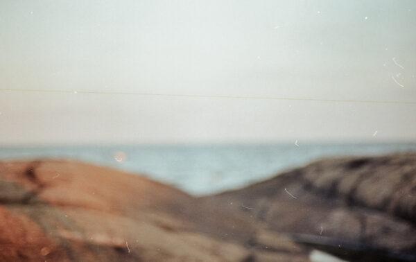 Oskarpt analogt fotografi av klippor vid en strand