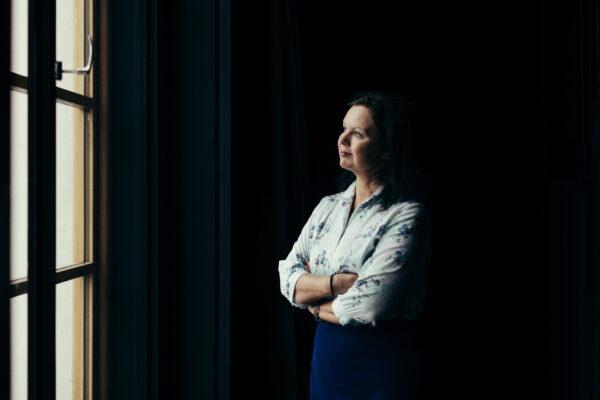 Porträtt av Ann-Luise Bertell mot mörk bakgrund som tittar ut genom fönstret