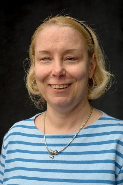 Porträtt av Tessa Bamberg, i blont hår och en ljusblå-randing skjorta.